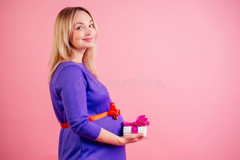 Очаровательная и нежная блондинка-беременная женщина, живот-бэби-бум, держит коробку с подарком в платье в студии на розовом стоковая фотография rf