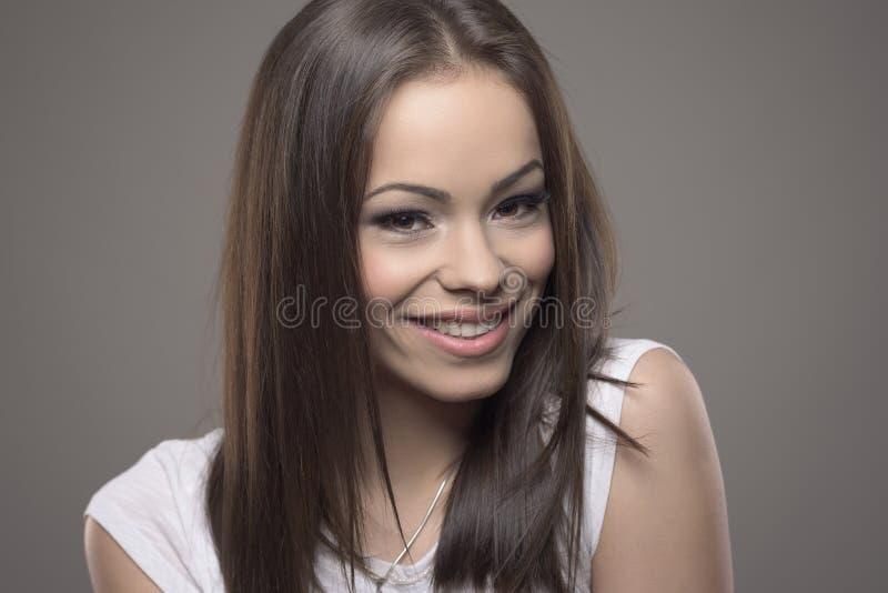 Очаровательная красивая молодая женщина брюнет усмехаясь и смотря камеру стоковое фото
