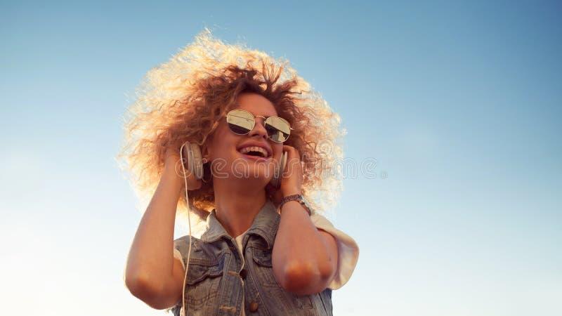 Очаровательная курчавая блондинка слушает к музыке большие детеныши женщины наушников outdoors портрет ультрамодной девушки стоковое изображение