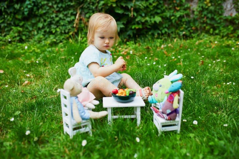 Очаровательная маленькая девочка, играющая с мягкими игрушками в парке или саду и готовящая их к ужину с фруктами и овощами-игруш стоковая фотография rf