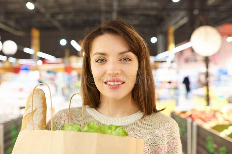 Очаровательная молодая женщина держа продуктовую сумку стоковая фотография rf