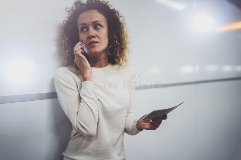 Очаровательная молодая женщина на переходе говоря на smartphone пока держащ с билетом перемещения руки в вокзале или airpot стоковая фотография