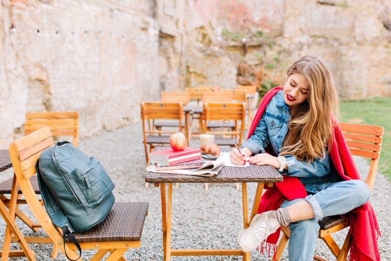 Очаровательная молодая женщина нося стильную куртку джинсовой ткани, наслаждается в воскресение утром и пишется личное письмо сид стоковые изображения