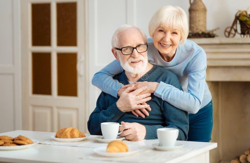 Очаровательная старшая женщина обнимая ее супруга стоковое изображение