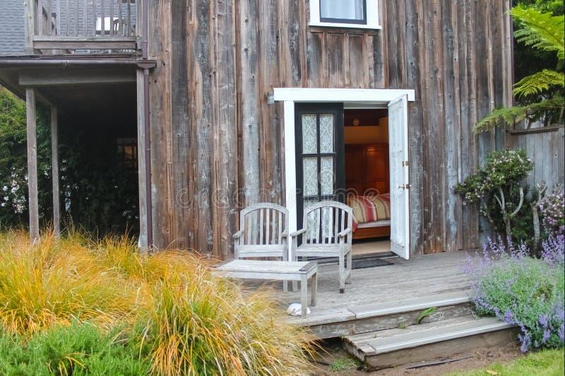 Очаровательная сцена - 2 выдержали деревянные стулья на крылечке вне открыть двери к спальне в деревенском доме окруженном завода стоковое фото rf