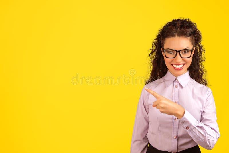 Очаровательное брюнет указывая прочь на желтый цвет стоковое изображение