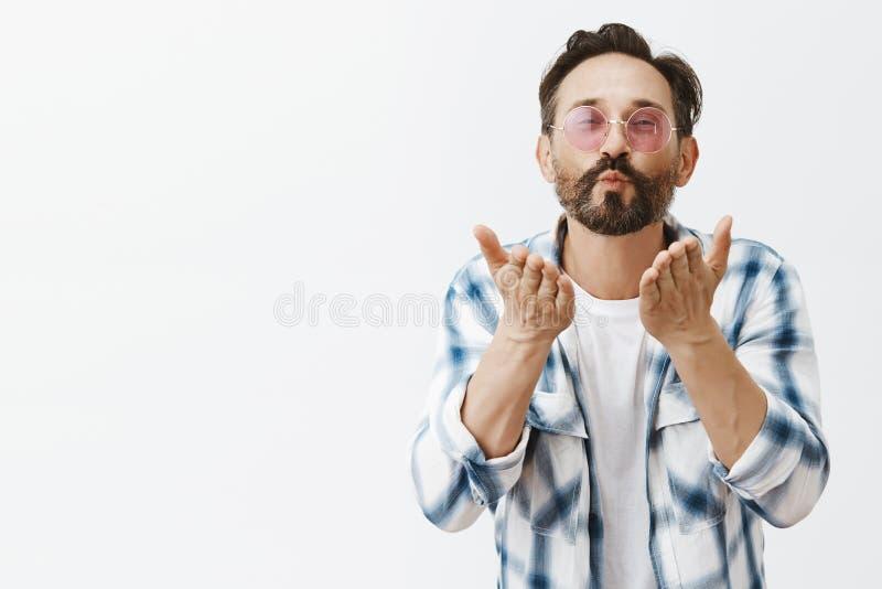 Очаровательный взрослый гомосексуалист с удовлетворенным счастливым выражением в ультрамодных солнечных очках и обхваченной рубаш стоковое фото rf