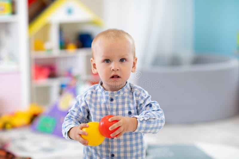 Очаровательный однолетний ребенок в игровой комнате Мальчик-ребёнок играет с цветными игрушками дома Раннее развитие, обучение и стоковые изображения
