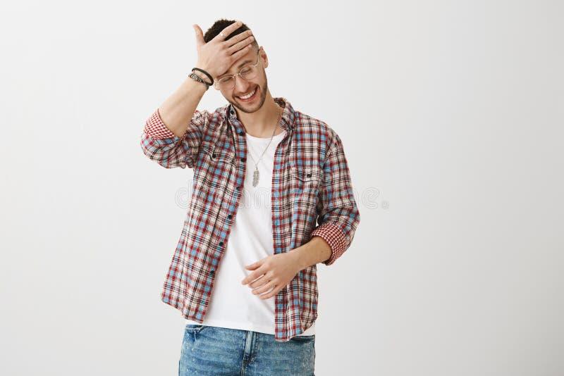 Очаровательный парень с лбом и смотреть затирания вкуса моды вниз пока усмехающся или смеющся над, конфузить с стоковое фото rf