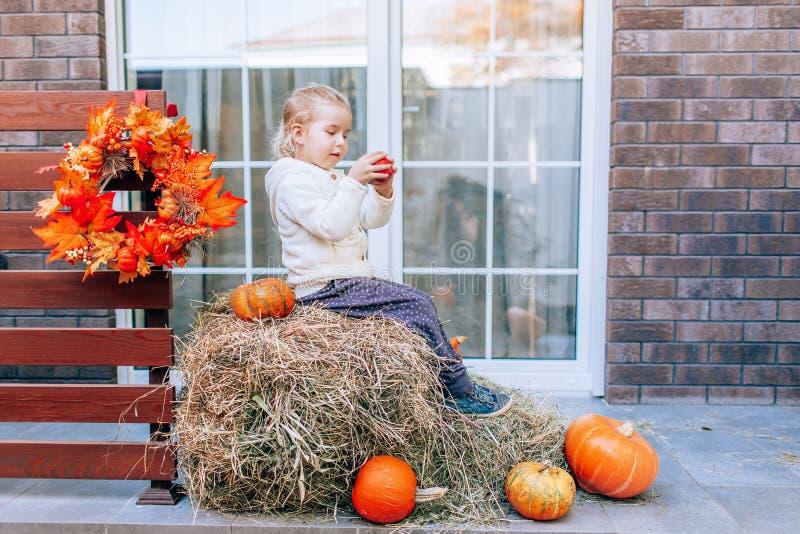 Очаровательный улыбающийся кавказский малыш в белой куртке, сидящий на стоге сена с тыквами на крыльце и играющий с стоковые фото