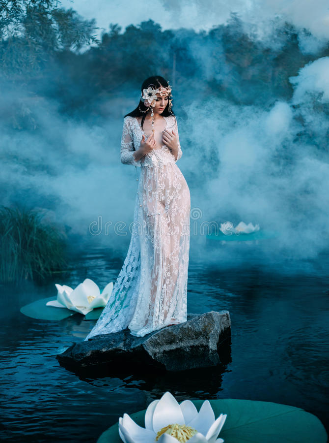 Очаровательная дама, стоя на огромном утесе в середине озера стоковые фотографии rf