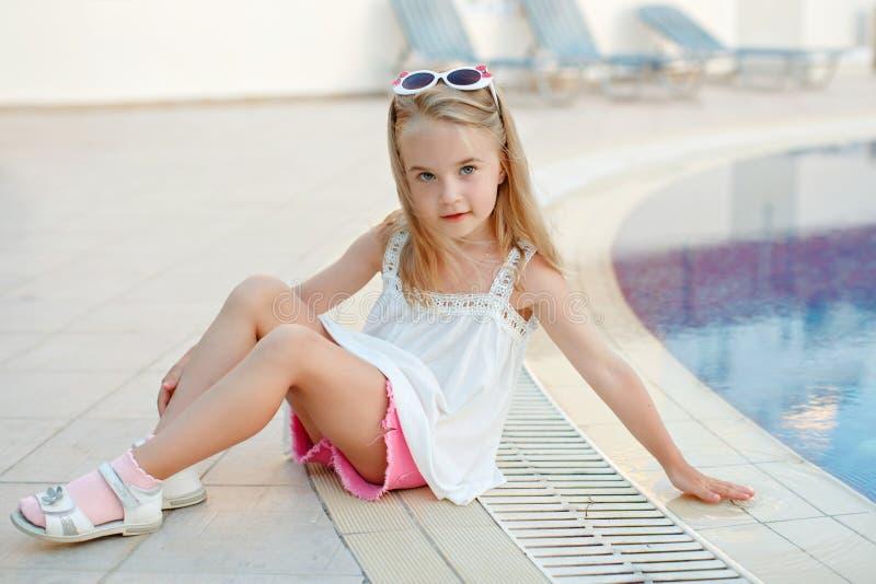 Очаровательная белокурая девушка в розовых шортах сидя вокруг бассейна в th стоковая фотография rf