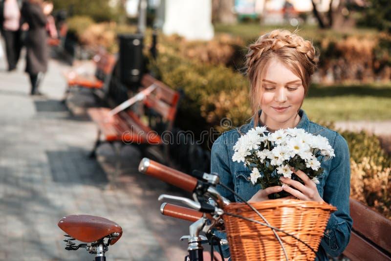 Очаровательная женщина при велосипед держа букет цветков на стенде стоковая фотография rf