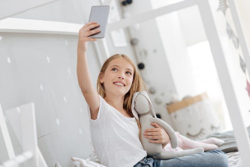 Очаровательная игрушка удерживания молодой дамы пока принимающ фото себя стоковое фото rf