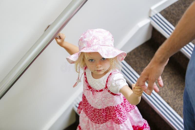 Очаровательная маленькая кавказская девушка в розовом флористическом платье смотря вверх, идущ вниз стоковые фото