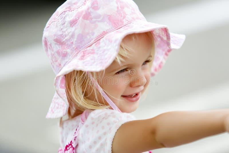 Очаровательная маленькая кавказская девушка в розовый усмехаться шляпы стоковое изображение
