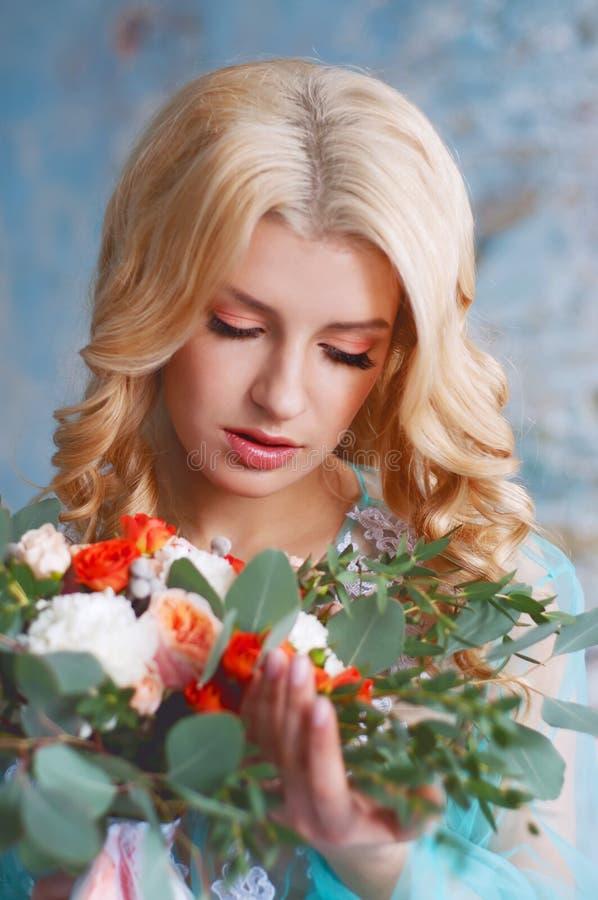 Очаровательная молодая белокурая женщина держа свежие цветки стоковая фотография rf