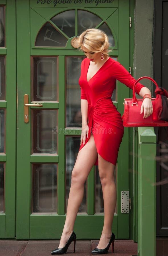 Очаровательная молодая блондинка в красном сексуальном платье представляя перед зеленым цветом покрасила дверную раму Чувственная стоковые фотографии rf