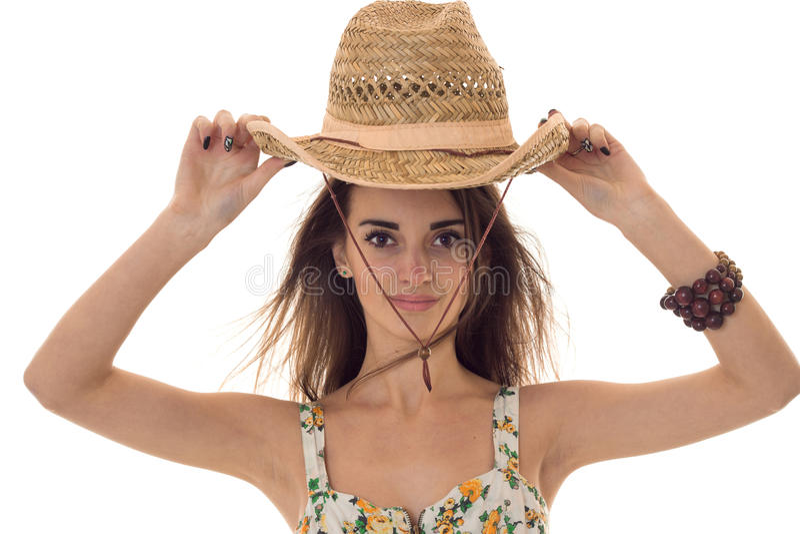 Очаровательная молодая девушка брюнет с соломенной шляпой и летом одевает при цветочный узор смотря камеру изолированную дальше стоковое фото rf