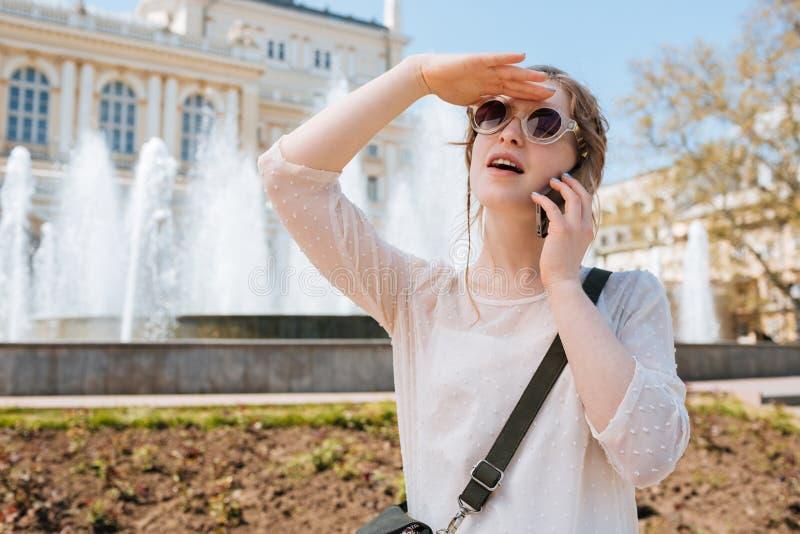 Очаровательная молодая женщина в солнечных очках говоря на мобильном телефоне outdoors стоковые изображения