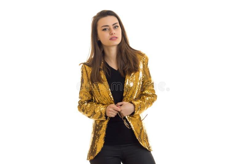 Очаровательная элегантная женщина в золотой куртке смотря камеру стоковые фото