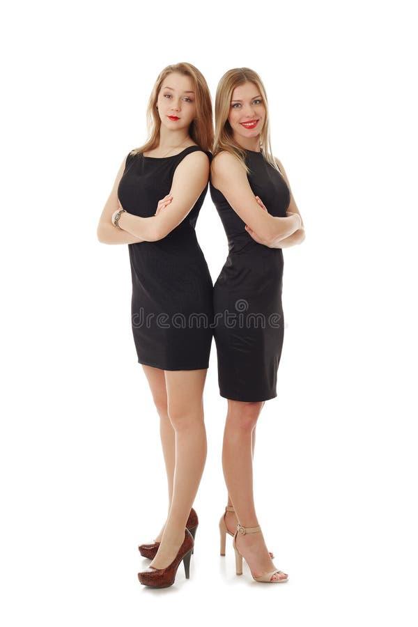 Очаровательные коллеги представляя стоять спиной к спине стоковое изображение