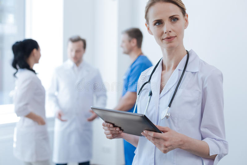 Очаровательный практикующий врач наслаждаясь профессиональными ответственностями на клинике стоковое фото rf