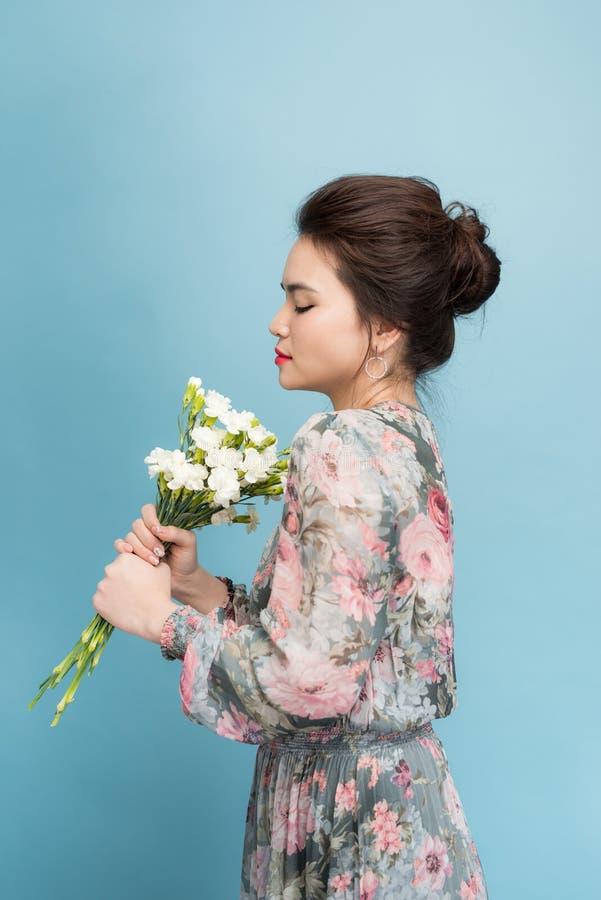 Очаровывая азиатская девушка в положении платья цветка на голубой предпосылке стоковые фото