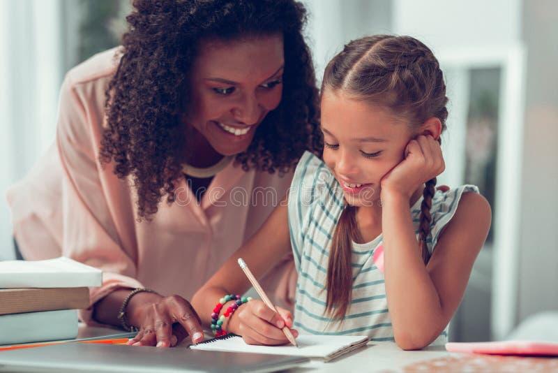 Очаровывая Афро-американская мать помогая ее сладкому schoolkid с домашней работой стоковые фото