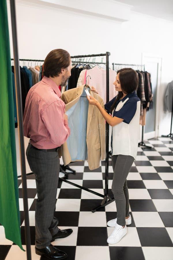 Очаровывая женщина проверяя цену бежевого блейзера стоковые фото