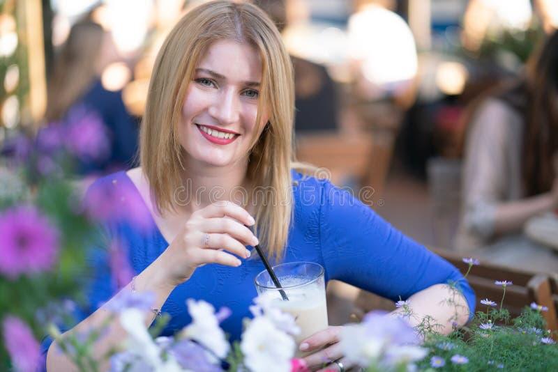 Очаровывая кавказская белокурая девушка в голубом платье сидя на таблице в кафе города самостоятельно и ожидании стоковое фото