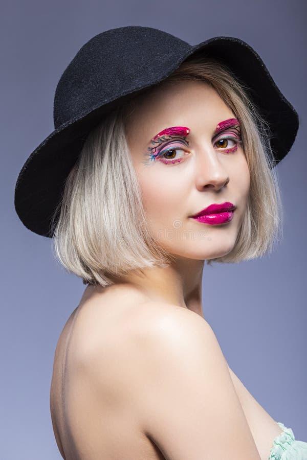 Очаровывая кавказская белокурая девушка в черной шляпе над серой предпосылкой с лицевым макияжем стоковое фото