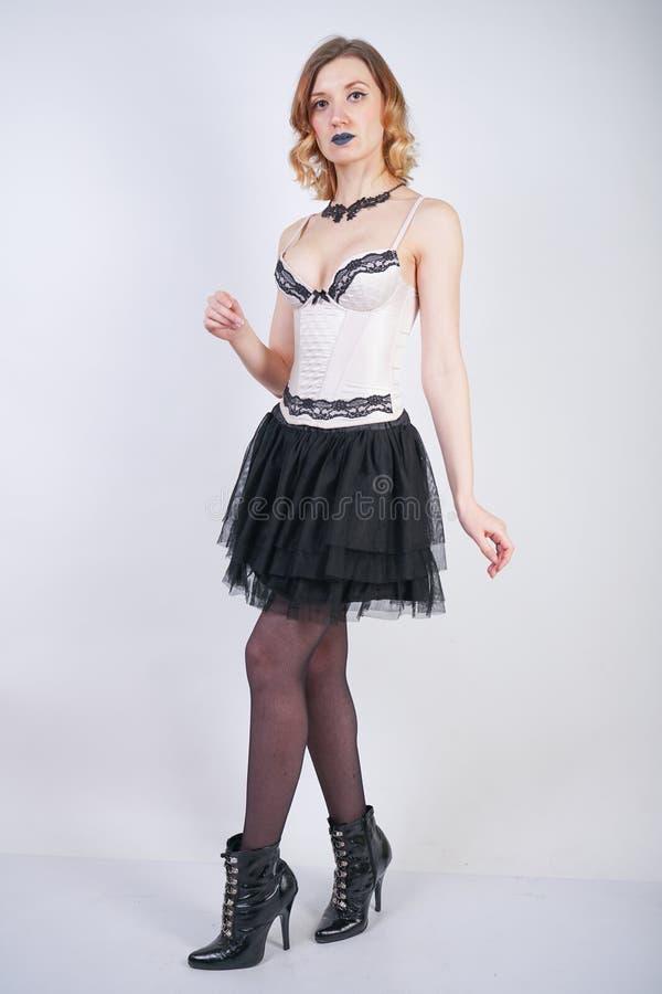 Очаровывая кавказская блондинка в лифе женского белья шнурка бежевом и черной юбке на белой предпосылке в студии стоковое фото rf