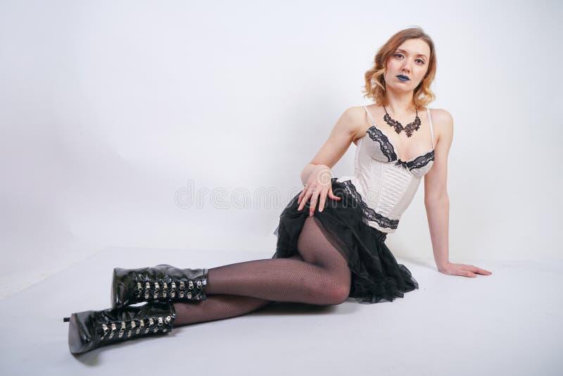 Очаровывая кавказская блондинка в лифе женского белья шнурка бежевом и черной юбке на белой предпосылке в студии стоковые фото