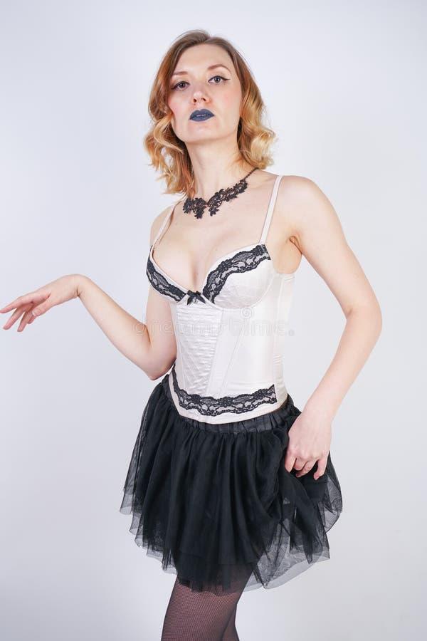 Очаровывая кавказская блондинка в лифе женского белья шнурка бежевом и черной юбке на белой предпосылке в студии стоковые изображения