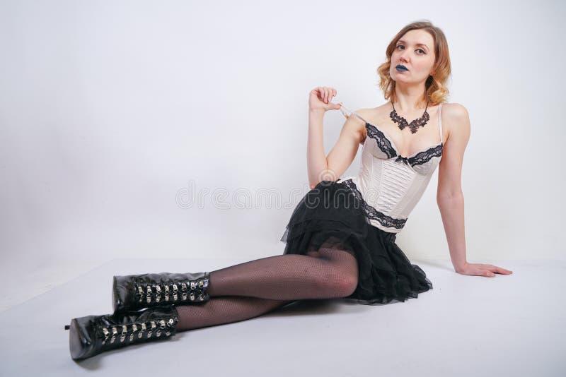 Очаровывая кавказская блондинка в лифе женского белья шнурка бежевом и черной юбке на белой предпосылке в студии стоковое изображение rf