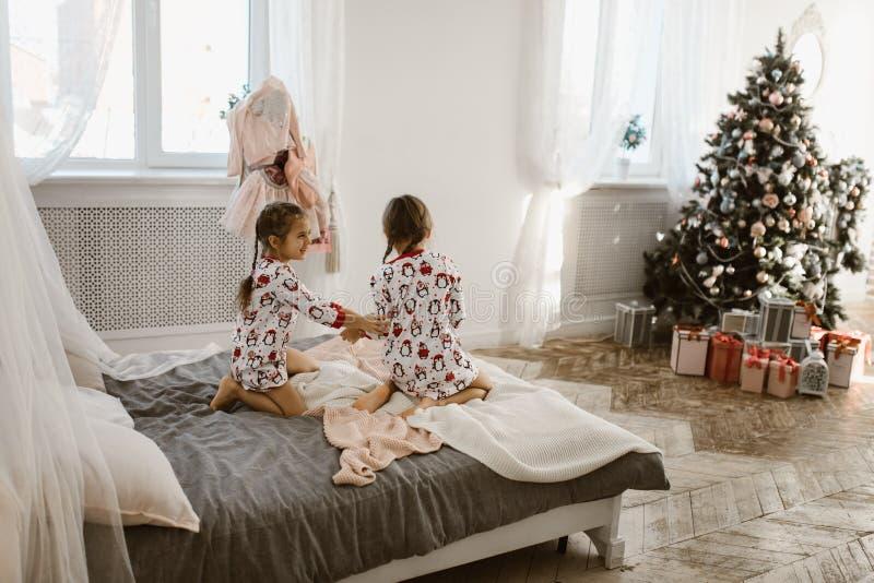 2 очаровывая маленькой девочки в их пижамах имеют потеху скача на кров стоковая фотография rf