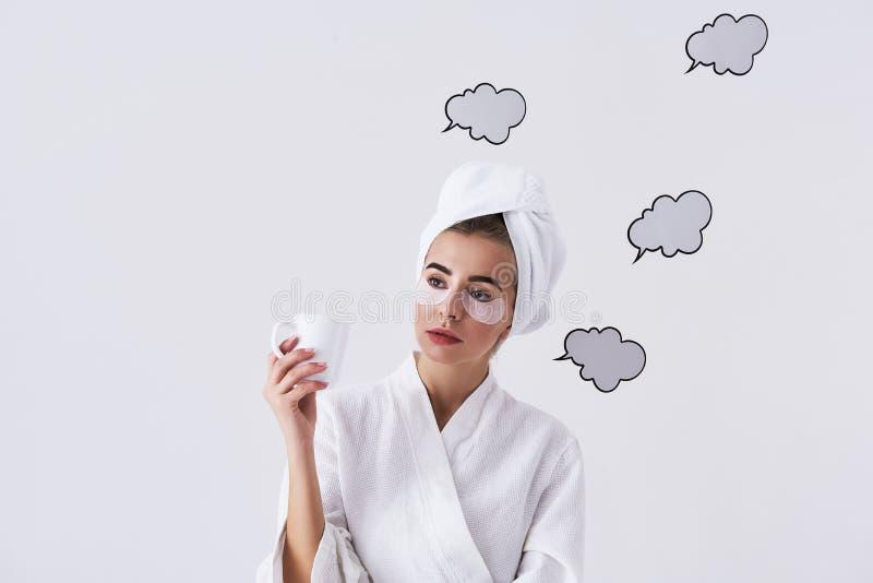 Очаровывая молодая дама с заплатами под глазами держа кофе и мысль стоковые фото