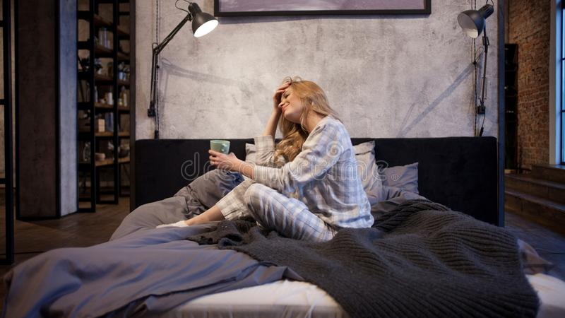 Очаровывая молодая женщина в пижамах, сидящ в кровати и выпивая кофе утра стоковое фото