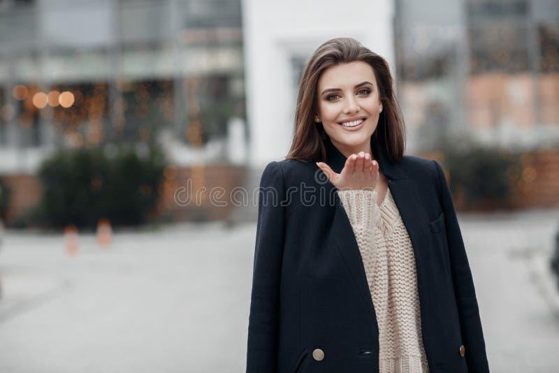 Очаровывая молодая женщина с красивыми глазами и естественный макияж в модных одеждах весны, представляя в городе на заходе солнц стоковое фото