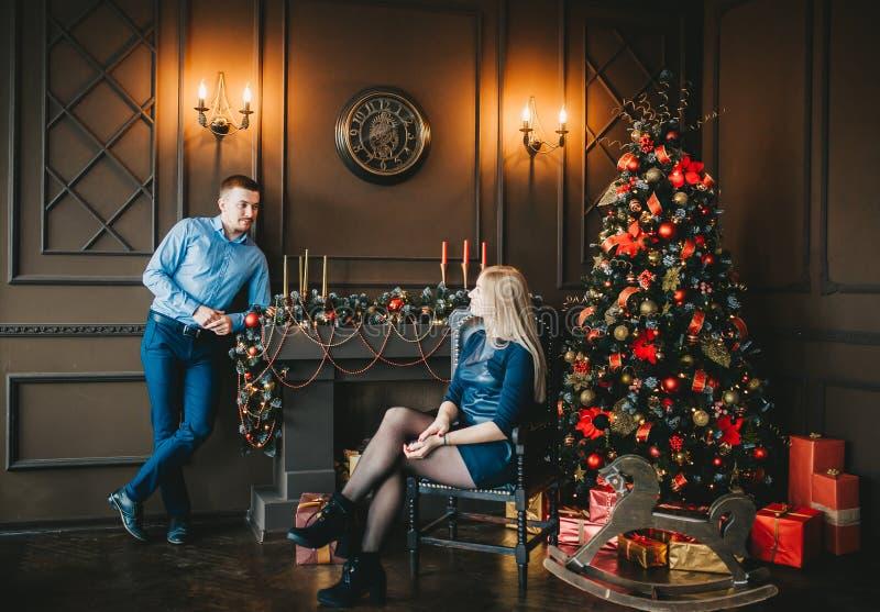 Очаровывая молодая пара в голубых одеждах представляет в комнате с рождественской елкой стоковая фотография rf
