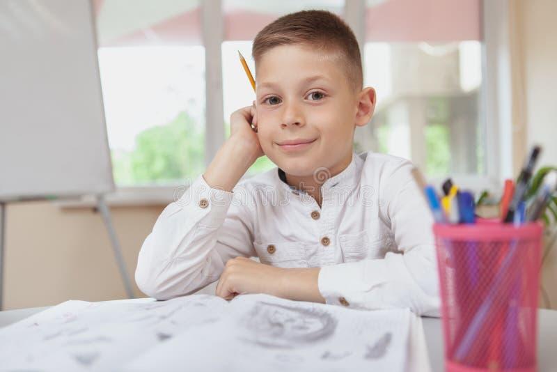Очаровывая молодой мальчик делая эскиз к в его учебнике стоковое изображение rf