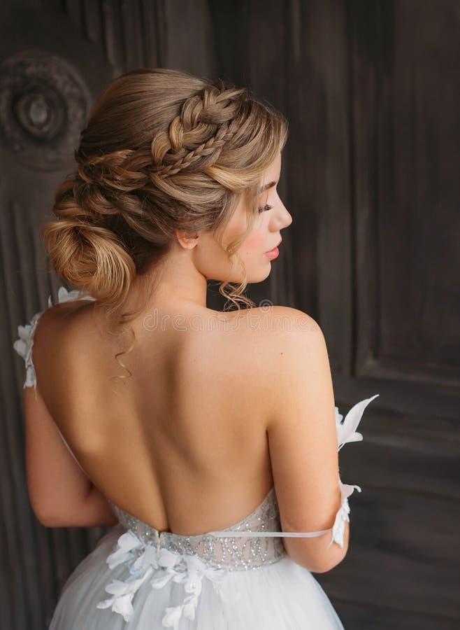 Очаровывая нежная принцесса стоит с ее задней частью к камере, мягким особенностям с профессиональным макияжем, великолепной бели стоковое фото rf