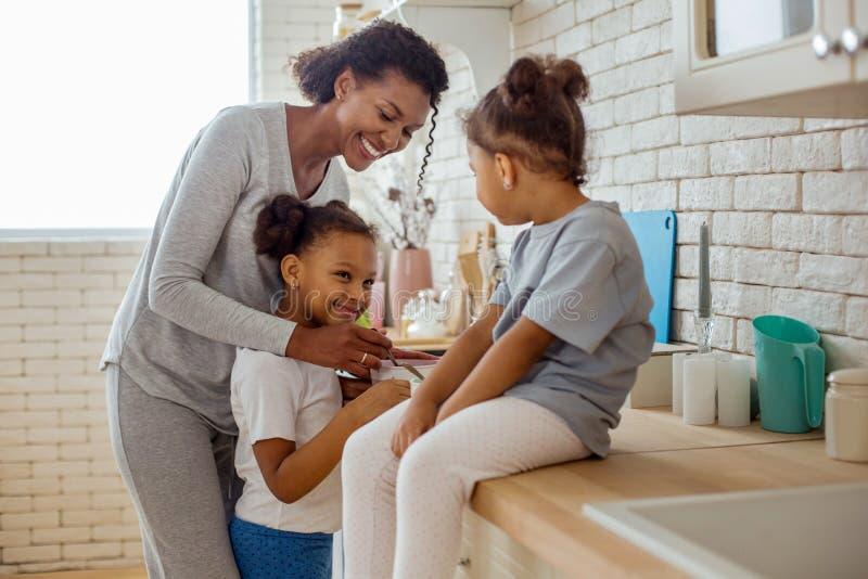 Очаровывая положение девушки около ее мамы и смотреть сестру стоковые фотографии rf
