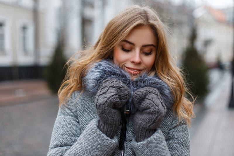 Очаровывая привлекательная блондинка молодой женщины в стильном теплом outerwear зимы в связанных mittens наслаждается выходными стоковое изображение rf