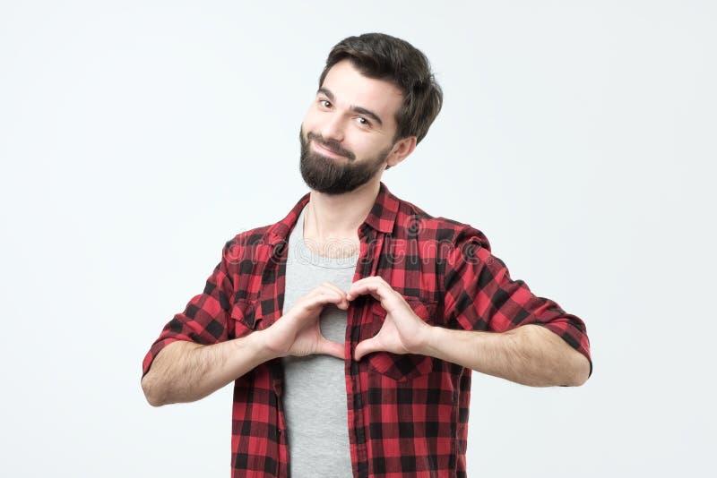 Очаровывая привлекательный испанский студент, держа руки в жесте сердца пока усмехающся стоковые фотографии rf