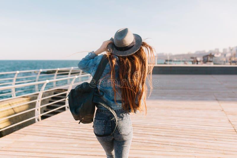 Очаровывая фотограф девушки с длинными волосами и стильным рюкзаком принимая фото восхитительного seascape Молодой брюнет стоковое изображение rf