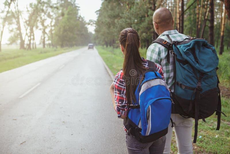 Очаровывая multiracial пары путешествуя автостопом совместно стоковая фотография rf