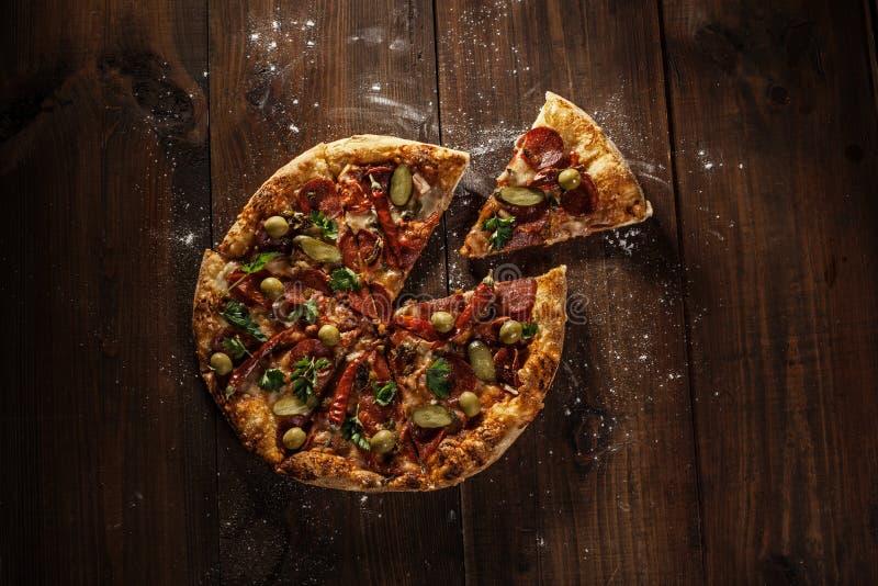 Очень вкусная итальянская пицца с куском служила на деревянном столе стоковое изображение