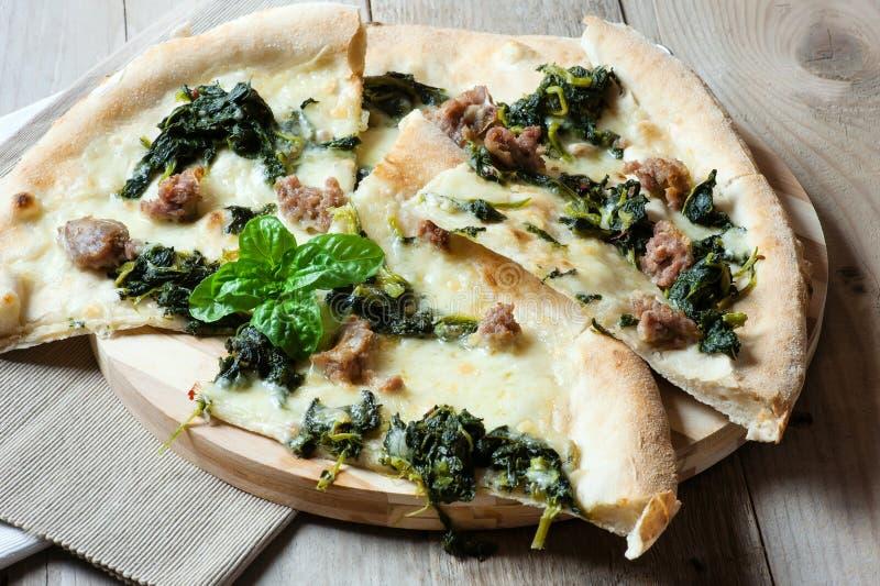 Очень вкусная итальянская пицца с моццареллой, сосиской и базиликом стоковое изображение rf